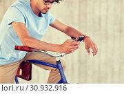 Купить «man with smartphone and fixed gear bike on street», фото № 30932916, снято 15 июня 2016 г. (c) Syda Productions / Фотобанк Лори