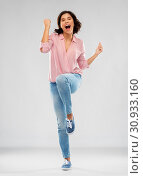 Купить «young woman in shirt and jeans celebrating success», фото № 30933160, снято 6 марта 2019 г. (c) Syda Productions / Фотобанк Лори