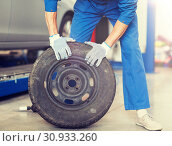 mechanic with wheel tire at car workshop. Стоковое фото, фотограф Syda Productions / Фотобанк Лори