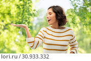 Купить «woman with empty hand over natural background», фото № 30933332, снято 6 марта 2019 г. (c) Syda Productions / Фотобанк Лори
