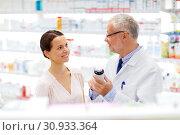 Купить «apothecary and woman with drug at pharmacy», фото № 30933364, снято 27 июня 2015 г. (c) Syda Productions / Фотобанк Лори