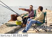 Купить «happy friends with fishing rods on pier», фото № 30933440, снято 8 сентября 2018 г. (c) Syda Productions / Фотобанк Лори