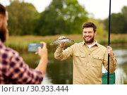Купить «friend photographing fisherman with fish at lake», фото № 30933444, снято 8 сентября 2018 г. (c) Syda Productions / Фотобанк Лори