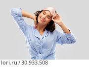 Купить «happy young woman in pajama and eye sleeping mask», фото № 30933508, снято 6 марта 2019 г. (c) Syda Productions / Фотобанк Лори