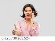 Купить «woman calling on smartphone and showing thumbs up», фото № 30933524, снято 6 марта 2019 г. (c) Syda Productions / Фотобанк Лори