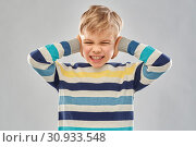 Купить «stressed boy in pullover closing ears by hands», фото № 30933548, снято 9 марта 2019 г. (c) Syda Productions / Фотобанк Лори