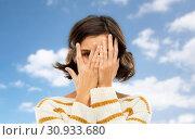 Купить «young woman looking by one eye through her fingers», фото № 30933680, снято 6 марта 2019 г. (c) Syda Productions / Фотобанк Лори