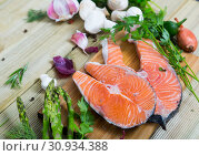 Купить «Salmon steaks with fresh vegetables and mushrooms on wooden background», фото № 30934388, снято 16 июня 2019 г. (c) Яков Филимонов / Фотобанк Лори