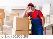 Купить «Young male contractor with boxes working indoors», фото № 30935288, снято 1 февраля 2019 г. (c) Elnur / Фотобанк Лори