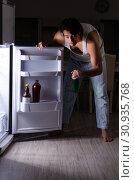Купить «Man breaking diet at night near fridge», фото № 30935768, снято 8 февраля 2019 г. (c) Elnur / Фотобанк Лори