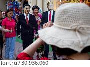 Купить «Китайские туристы фотографируются рядом со статуями лидера Китая Си Цзиньпиня и президента США Дональда Трампа на Арбате в центре города Москвы, Россия», фото № 30936060, снято 8 июня 2019 г. (c) Николай Винокуров / Фотобанк Лори