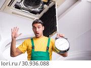 Купить «Young repairman repairing ceiling air conditioning unit», фото № 30936088, снято 27 февраля 2019 г. (c) Elnur / Фотобанк Лори