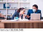 Купить «Two employees suffering at workplace», фото № 30936548, снято 15 апреля 2019 г. (c) Elnur / Фотобанк Лори