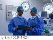 Купить «Surgeons discussing over medical report in operation theater», фото № 30941624, снято 9 марта 2019 г. (c) Wavebreak Media / Фотобанк Лори