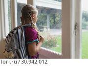 Купить «Cute girl with school bag looking outside through window in a comfortable home», фото № 30942012, снято 12 марта 2019 г. (c) Wavebreak Media / Фотобанк Лори