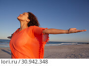 Купить «Beautiful woman with arms stretched out standing on beach in the sunshine», фото № 30942348, снято 15 марта 2019 г. (c) Wavebreak Media / Фотобанк Лори