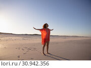 Купить «Woman with arms stretched out standing on beach in the sunshine», фото № 30942356, снято 15 марта 2019 г. (c) Wavebreak Media / Фотобанк Лори