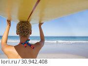 Купить «Woman in bikini carrying the surfboard on her head at beach in the sunshine», фото № 30942408, снято 15 марта 2019 г. (c) Wavebreak Media / Фотобанк Лори