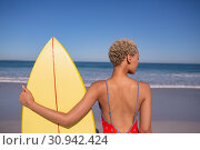 Купить «Woman in swimwear standing with surfboard on beach in the sunshine», фото № 30942424, снято 15 марта 2019 г. (c) Wavebreak Media / Фотобанк Лори
