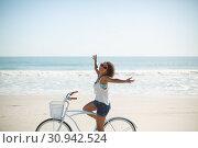 Купить «Woman riding bicycle with arms outstretched on the beach», фото № 30942524, снято 15 марта 2019 г. (c) Wavebreak Media / Фотобанк Лори