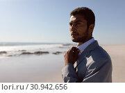 Купить «Young Businessman adjusting his tie on the beach», фото № 30942656, снято 15 марта 2019 г. (c) Wavebreak Media / Фотобанк Лори