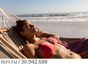 Купить «Woman in bikini sleeping in a hammock on the beach», фото № 30942688, снято 15 марта 2019 г. (c) Wavebreak Media / Фотобанк Лори