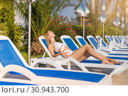Купить «Young beautiful girl in a bathing suit resting on a lounger on a tropical resort with palm trees», фото № 30943700, снято 18 июля 2017 г. (c) katalinks / Фотобанк Лори
