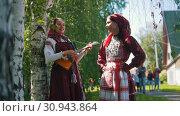 Купить «Women in national Russian costumes stand near birch one of them plays the balalaika.», видеоролик № 30943864, снято 22 июля 2019 г. (c) Константин Шишкин / Фотобанк Лори