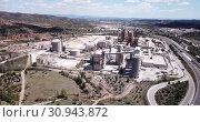 Купить «Aerial view of a huge cement plant with warehouses in Bunol, Valencia, Spain», видеоролик № 30943872, снято 24 апреля 2019 г. (c) Яков Филимонов / Фотобанк Лори