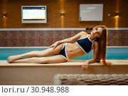 Купить «Woman in swimsuit lying at the pool indoors», фото № 30948988, снято 16 апреля 2019 г. (c) Tryapitsyn Sergiy / Фотобанк Лори