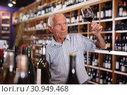 Купить «Man tasting wine in wine store», фото № 30949468, снято 8 мая 2019 г. (c) Яков Филимонов / Фотобанк Лори