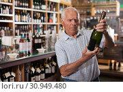 Купить «Man searchng wine in winehouse», фото № 30949480, снято 8 мая 2019 г. (c) Яков Филимонов / Фотобанк Лори