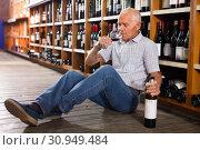 Купить «Portrait of senior man sitting on floor in winery tasting room, drinking red wine», фото № 30949484, снято 8 мая 2019 г. (c) Яков Филимонов / Фотобанк Лори