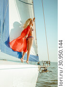 Купить «Young beautiful slim sexy girl in bikini and pareo is resting on cruise on a private sailing yacht», фото № 30950144, снято 25 июля 2017 г. (c) katalinks / Фотобанк Лори