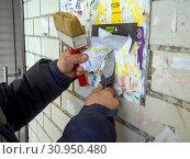 Купить «Очистка рекламного щита от старых объявлений», фото № 30950480, снято 14 марта 2019 г. (c) Вячеслав Палес / Фотобанк Лори