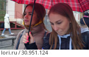Купить «Two female best friend walking on famouse Nilolskaya street with red umbrella», видеоролик № 30951124, снято 11 июня 2019 г. (c) Ирина Мойсеева / Фотобанк Лори
