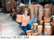 Купить «Young woman customer looking decorative clay pot for garden», фото № 30951248, снято 23 июля 2019 г. (c) Яков Филимонов / Фотобанк Лори