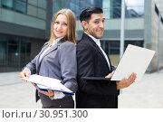 Купить «Portrait of couple professionals who are posing with laptop and folder», фото № 30951300, снято 20 августа 2017 г. (c) Яков Филимонов / Фотобанк Лори