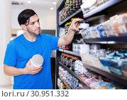 Купить «Serious muscular sportman choosing sport supplements in shop», фото № 30951332, снято 28 марта 2018 г. (c) Яков Филимонов / Фотобанк Лори