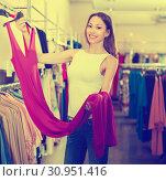 Купить «young smiling brunette selecting new dress in fashionable showroom», фото № 30951416, снято 11 апреля 2017 г. (c) Яков Филимонов / Фотобанк Лори