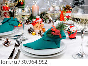 Napkin folded in the form of an Elven boot decorated on the Christmas table. Стоковое фото, фотограф Maryna Voronova / easy Fotostock / Фотобанк Лори