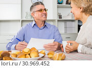 smiling mature couple at table attentively study documents. Стоковое фото, фотограф Яков Филимонов / Фотобанк Лори