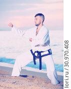 Купить «Brunette man doing karate at ocean quay», фото № 30970408, снято 19 июля 2017 г. (c) Яков Филимонов / Фотобанк Лори