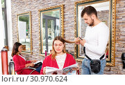 Positive young man hairdresser cuts hair of young woman with magazine at salon. Стоковое фото, фотограф Яков Филимонов / Фотобанк Лори