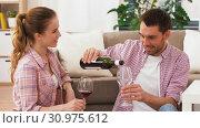 Купить «happy couple drinking red wine at home», видеоролик № 30975612, снято 10 июня 2019 г. (c) Syda Productions / Фотобанк Лори