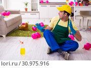 Купить «Young male contractor doing housework after party», фото № 30975916, снято 14 марта 2019 г. (c) Elnur / Фотобанк Лори