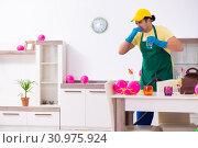 Купить «Young male contractor doing housework after party», фото № 30975924, снято 14 марта 2019 г. (c) Elnur / Фотобанк Лори