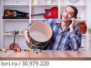 Купить «Young handsome repairman repairing drum», фото № 30979220, снято 4 апреля 2019 г. (c) Elnur / Фотобанк Лори