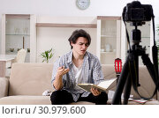 Купить «Young guitar player recording video for his blog», фото № 30979600, снято 17 января 2019 г. (c) Elnur / Фотобанк Лори