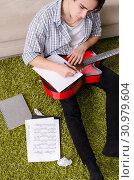Купить «Young man with guitar at home», фото № 30979604, снято 17 января 2019 г. (c) Elnur / Фотобанк Лори